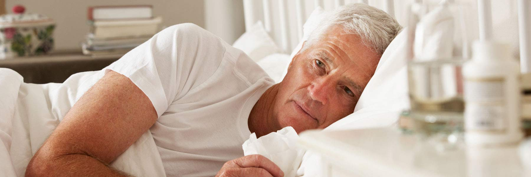 Older man lying awake in bed