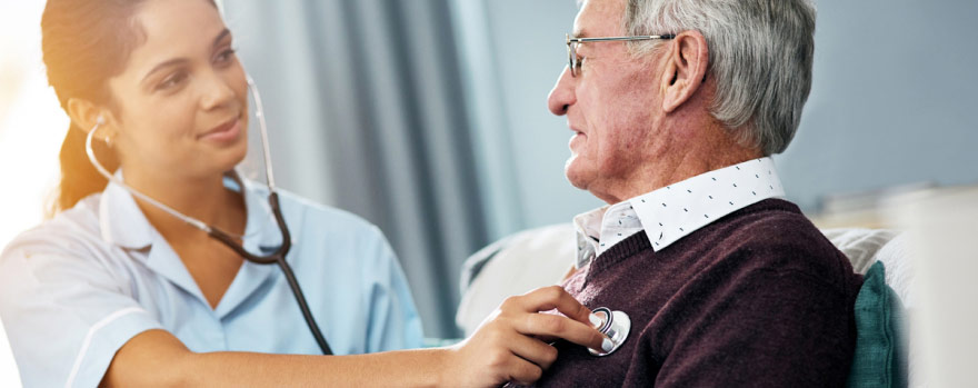 Nurse listening to a elderly man's heart with a stethoscope