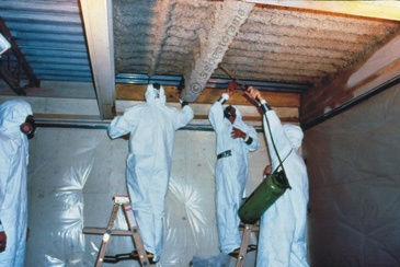 Men in suits removing asbestos from ceiling.