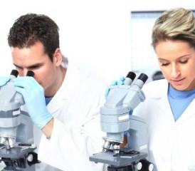 Male and female scientists looking through microscopes