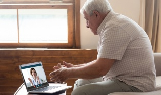Older man on a video call with his caregiver on a computer