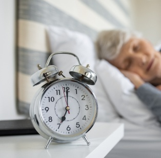 Older woman sleeping next to an alarm clock