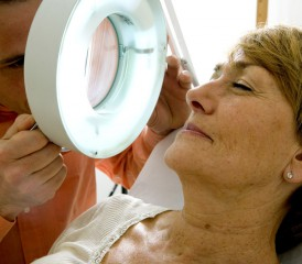 Dermatologist examining a woman's face