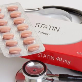 Pink pills in plastic with box that says statins and a stethoscope