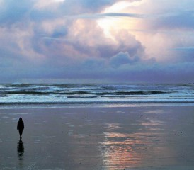 Person Walking Alone on Beach