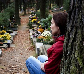 Woman grieving against a tree in a cemetery