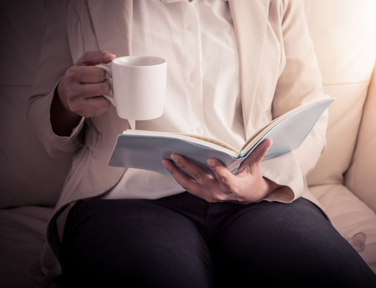Woman relaxing on sofa and reading book while holding cup